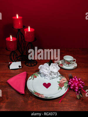 Floral pattern fine china dinnerware with matching plate, cup and saucer. bouquet of white roses, pink napkin, silverware, red candles and card - Stock Image