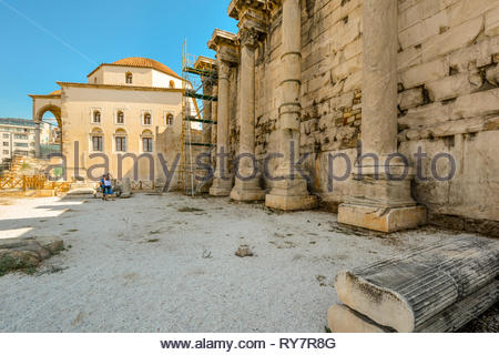 A young couple sightseeing visit the ancient ruins of Hadrian's Library Wall in the Plaka district of Athens, Greece on a sunny summer day - Stock Image
