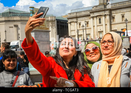 Trafalgar Square, London, UK, 08th June 2019. Selfie time on the square. Thousands of Londoners and visitors come together on Trafalgar Square to celebrate the end of Ramadan and Eid Festival, as well as London's rich cultural diversity. The festival is hosted by Mayor of London Sadiq Khan. - Stock Image