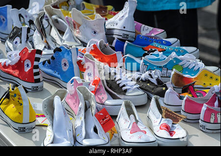 A table of  funky athletic shoes footwear sneakers for sale - Stock Image