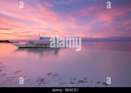 Sunset view of the Dolho Beach with traditional bangka boat, Panglao, Bohol, Philippines - Stock Image