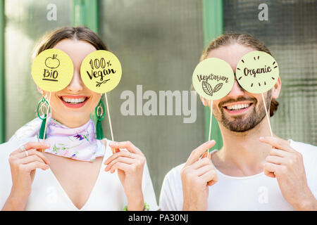 Young couple holding green plates with healthy eating slogans outdoors on the green background - Stock Image