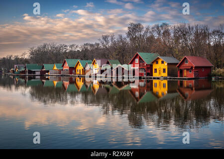 Tata, Hungary - Fishing cottages by the Lake Derito (Derito to) at sunset with reflections and colourful sky and clouds - Stock Image