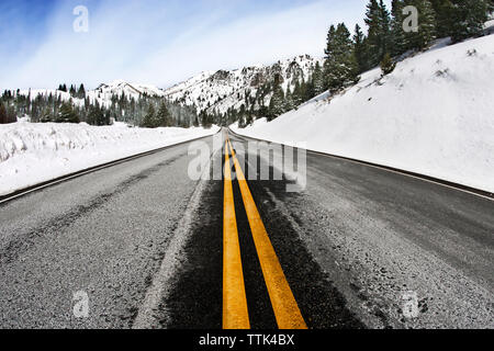 Empty road leading towards snow covered mountains - Stock Image