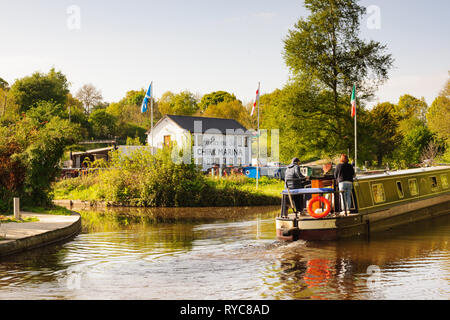 A canal barge with holiday makers passing the Chirk Marina on the Llangollen canal in North Wales - Stock Image