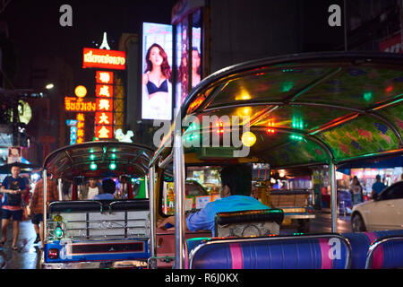 Night shot of traditional colourful tuk-tuk motorbike in Chinatown district in Bangkok, Thailand, with neon signs in the background. - Stock Image