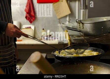 Chef at Chinese takeaway kitchen cooking king fried prawns. - Stock Image