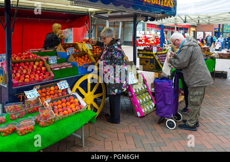 Elderly customers at a greengrocer and fruiterers market stall in Redcar Town Centre - Stock Image