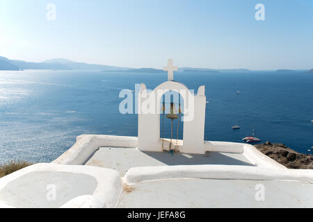 Beautful white chapel at Santorini and in the background the view of caldera - Stock Image