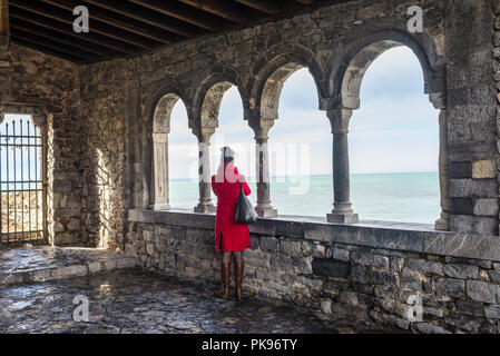 Woman dressed in red coat admiring the Mediterranean sea from the loggia of San Pietro, Portovenere, Cinque Terre, Liguria, Italy - Stock Image