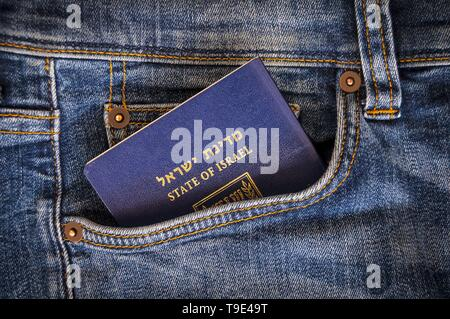 A blue passport of the State of Israel sticking from a pocket of blue denim jeans. Israeli tourist travel, Israel citizenship, Israeli biometric - Stock Image