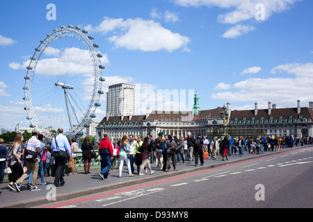 Lots of tourists crossing Westminster bridge, London England. - Stock Image