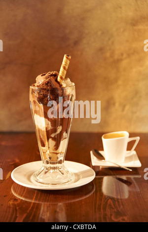 A still life shot of a chocolate sundae and a cup of espresso - Stock Image