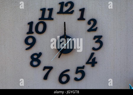 Big clock on white wall with black numbers. - Stock Image