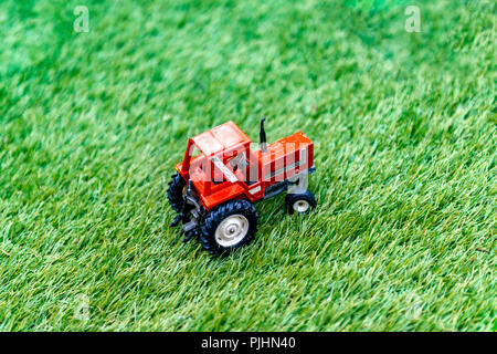 Miniature toy tractor on fake grass - Stock Image