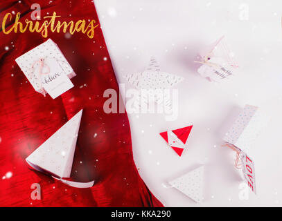 Christmas Decoration with different gift boxes and red scarves cloth with snow for holidays best background image - Stock Image