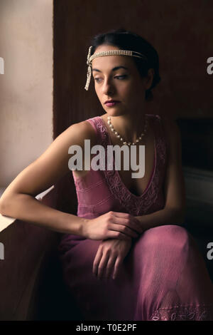 Beautiful woman in authentic retro twenties flapper dress and headband looking out of a window - Stock Image
