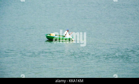 Man sailing a small round boat in the water reservoir to catch fish in the water - Stock Image