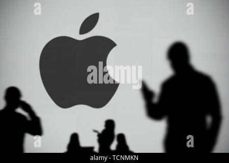 The Apple logo is seen on an LED screen in the background while a silhouetted person uses a smartphone in the foreground (Editorial use only) - Stock Image