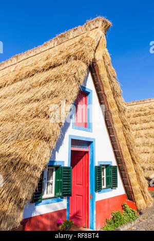 Palheiro house Santana Madeira Traditional triangular A-framed Palheiro Houses Santana Madeira Portugal red blue and white painted house portuguese - Stock Image