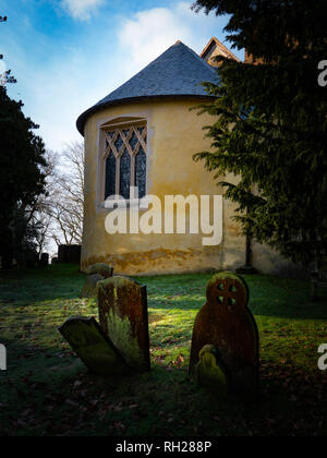 Portrait English village church with cemetery tombstones in early morning sunlight - Stock Image
