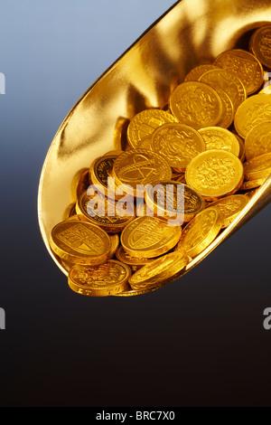 Golden scoop of money, close-up - Stock Image