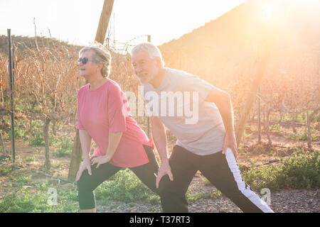 Happy active couple of old senior cacuasian people man and woman do fitness stretching for healthy lifestyle outdoor leisure activity - sunlight in ba - Stock Image