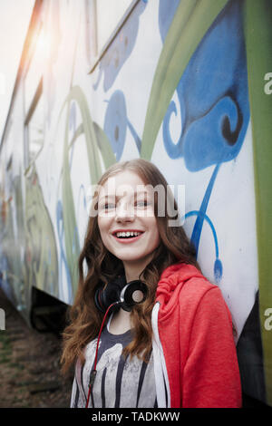 Portrait of happy teenage girl at a painted train car - Stock Image