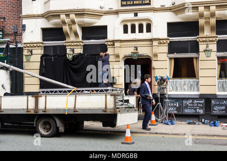 TV/movie lighting equipment and blackout material being set up outside the Old White Lion pub, Bury,  in preparation for the filming of 'Bancroft'. - Stock Image