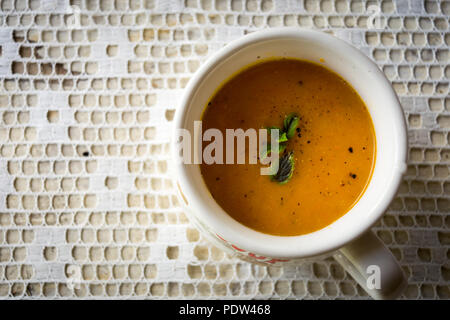 Soup with carrots, ginger and orange juice decorated with mint seen from above - Stock Image