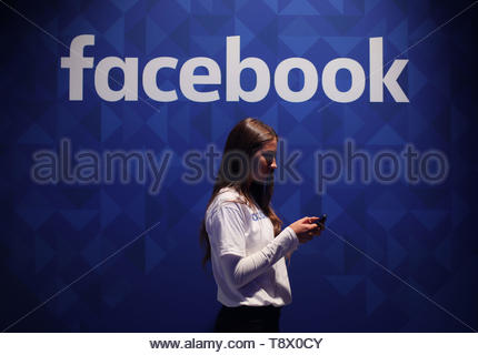 File photo dated 03/11/15 of a woman using her phone under a Facebook logo. The social networking giant will restrict people who have broken certain rules from using its Live streaming feature, in response to the mosque terror attack in Christchurch, New Zealand. - Stock Image