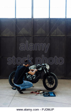 Young man kneeling to do maintenance on vintage motorcycle in empty warehouse - Stock Image
