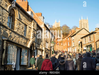 Crowds of people climbing Steep Hill at Lincoln Christmas Market, Lincolnshire, England, UK - Stock Image