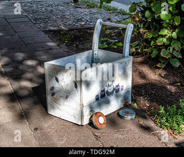 Broken toy cart abandoned or dumped on a city pavemt in Mitte, Berlin. The wheels came off concept - Stock Image