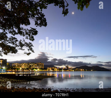 Scenic view of the city of Cairns at nighttime with the bay illuminated and the moon visible, Far North Queensland, FNQ, QLD, Australia - Stock Image