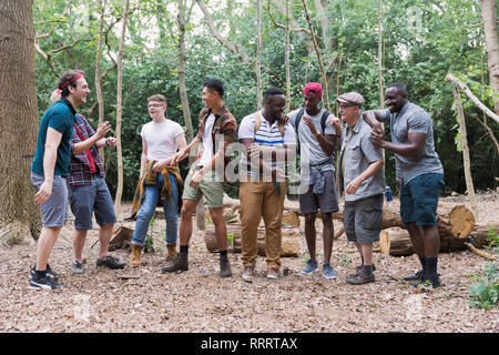 Mens group talking, hiking in woods - Stock Image