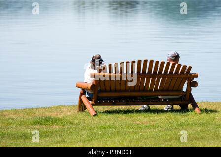 A man and woman sitting on a park bench at Osborne Point on Lake Pleasant at Speculator, NY USA enjoying nature. - Stock Image