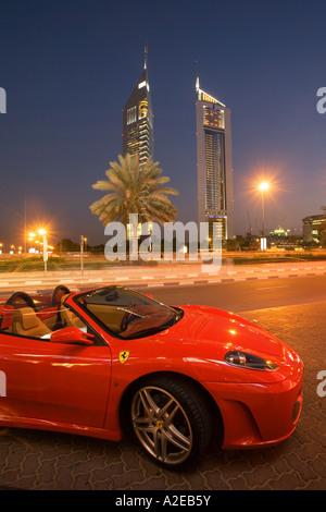 Dubai Sheikh Zayed Road skyscraper Emirates towers skyline Ferrari - Stock Image