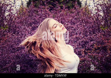 Young woman with long straight hair on flowers background - Stock Image