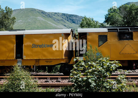 Stoneblower railway track maintenance machine for levelling the track, at Bridge of Orchy station on the West Highland Line, Scotland - Stock Image