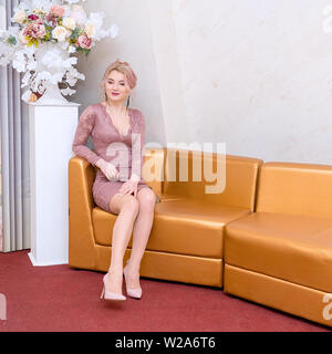 Beautiful young woman in a short evening dress sitting on sofa - Stock Image