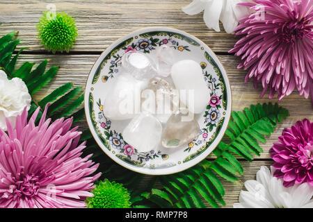 Decorative Plate with Clear Quartz, Snow Quartz and Spring Flowers - Stock Image