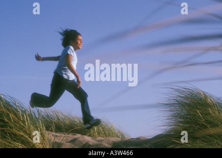 8 year old Hispanic girl running on beach - Stock Image
