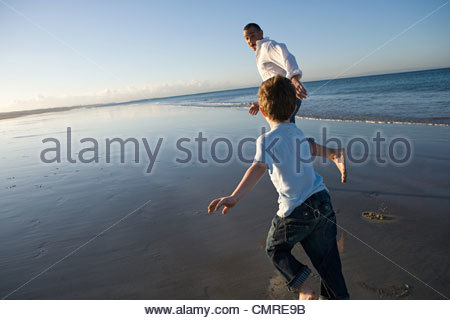 Father and son running by the sea - Stock Image
