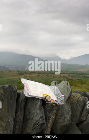 Ordnance Survey map in a plastic case with a compass on a drystone wall in the Lake District, overlooking a cloudy and misty Broughton Moor in Furness. - Stock Image