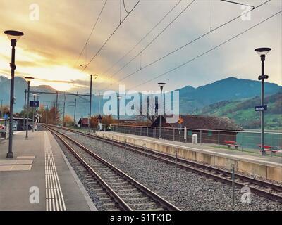 Railway track at sunset in Switzerland - Stock Image