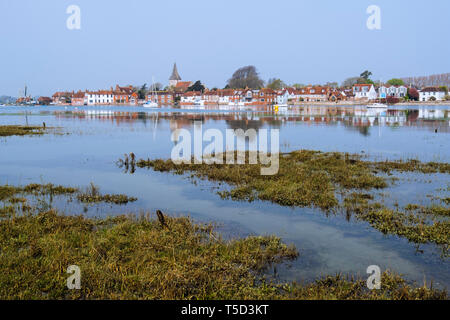 Village reflected in still waters of Bosham Creek at high tide in Chichester harbour. Bosham, West Sussex, England, UK, Britain, Europe - Stock Image