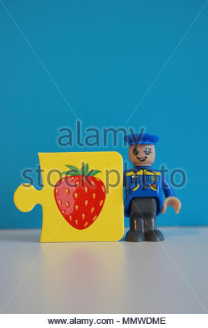 Playtive Junior mailman figure standing next to a puzzle piece with strawberry illustration - Stock Image