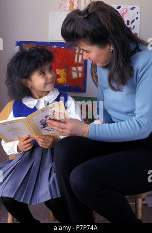 mother or teacher reading with little girl - Stock Image