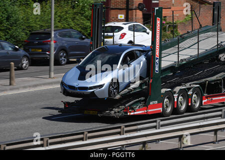 A BMW I8 series car on back of trailer being transported. - Stock Image